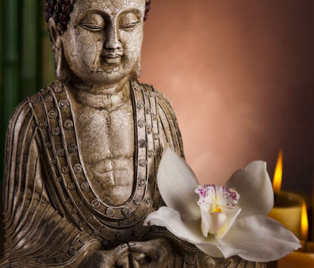Buddha statue with orchid flower photo