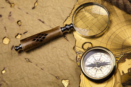 Antique brass compass over old map photo