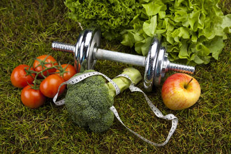 Vitamin and Fitness diet, dumbell in green grass  photo
