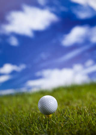 Golf ball on green grass over a blue sky photo