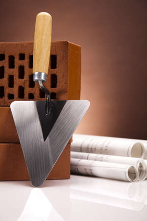 Brick, trowel tool and Construction plans photo