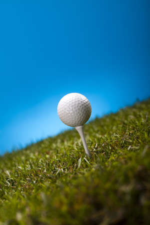 Golf ball on green grass over a blue background Stock Photo - 17487061