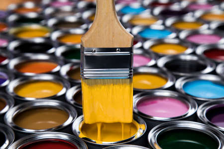 Tin metal cans with color paint and paintbrush