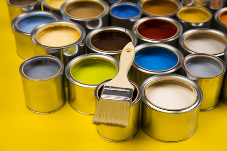 Metal tin cans with color paint and paintbrush Imagens