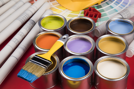 Collection of colored paints cans, Brush, red background