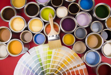 Colección de latas de pinturas de colores, pincel, fondo rojo.