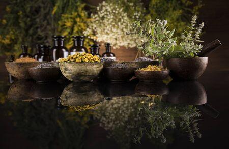 Alternative health, fresh herbal and mortar in black mirror background