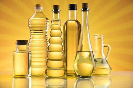 Olive oil, rapeseed oil, sunflower oil on sunburst orange background