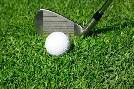 Golf club with golf ball on a grass photo