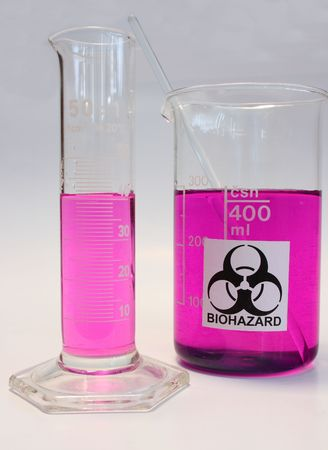 Glass beaker with biohazard sign and graduated cylinder filled with violet liquid