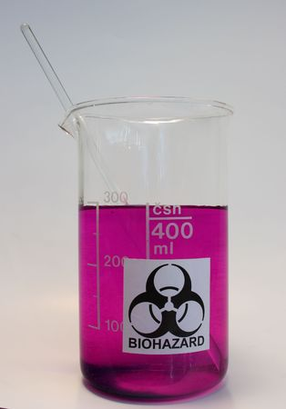 stiring: Biohazard sign on glass beaker with violet liquid and stiring rod Stock Photo