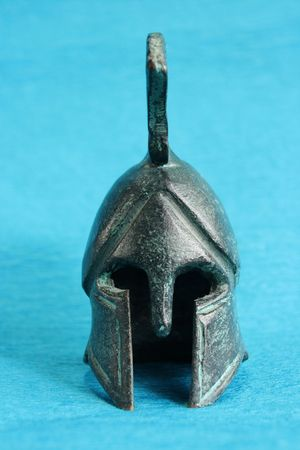 ancient greek helmet isolated on blue background photo