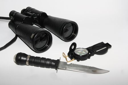 Tubular compass, binoculars and blackened knife isolated on a white background Stock Photo - 1479874