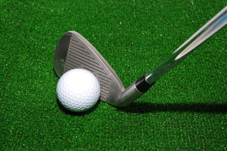 Golf club and ball on artificial grass