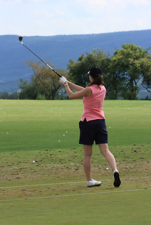 Young female golfer in the middle of swing
