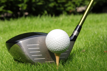 Golf ball on a tee with driver Stock Photo