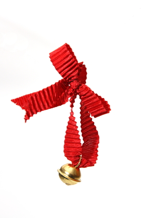 customs and celebrations: christmas jingle bell hanging on red ribbon on white background Stock Photo