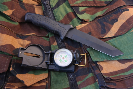 Tubular compass, and blackened knife laying on a camoflaged vest