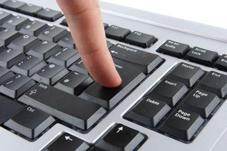Finger pressing enter on black computer keyboard Stock Photo