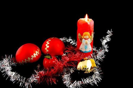 Red christmas ball decorated with gold with christmas apples and lit red christmas candle photo