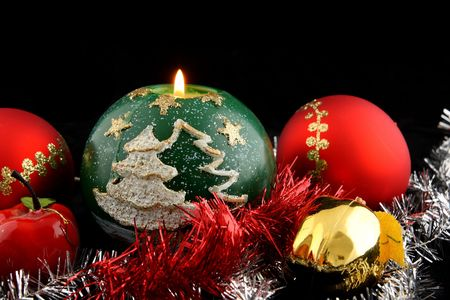 Red christmas ball decorated with gold with christmas apples and lit green christmas candle Stock Photo - 2102229