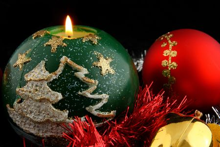 Red christmas ball decorated with gold and lit green christmas candle