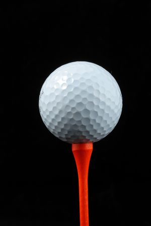 White golf ball on red tee photo