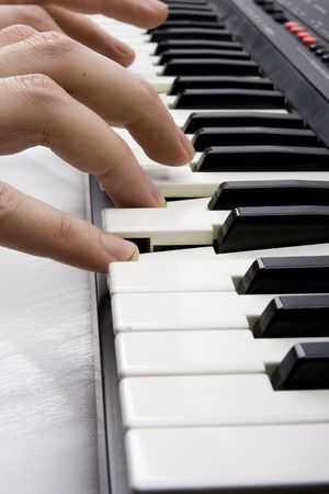 Macro of hands playing music on piano