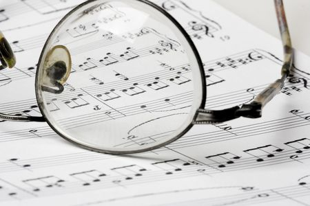 chorale: Close up photo of glasses on sheet music