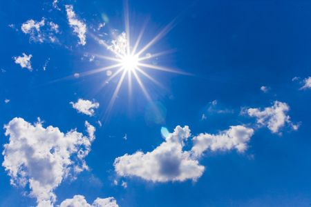 A dramatic blue sky with white clouds and sun Stock Photo