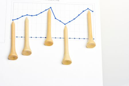 Golf business concept - golf tees pointing on graph Stock Photo