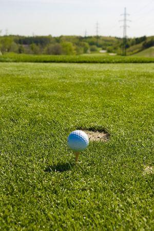 White golf ball on a tee photo