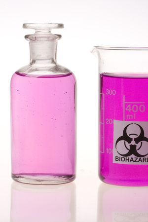laboratory flask and beaker with biohazard symbol filled with violet liquid on white background photo