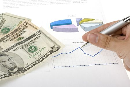hand with pen showing report with diagrams and american dollars Stock Photo