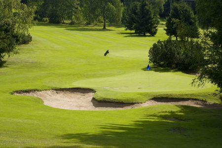 golf green: Golf course with golf hole and flag Stock Photo