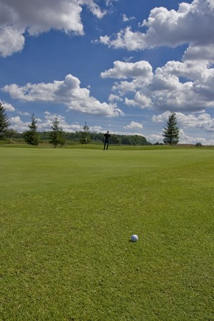golf ball on a green of a beautiful golf course with golfer in behind under dramatic summer sky photo