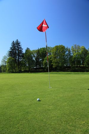 golf ball next to a flag on a green of a beautiful golf course with dramatic summer sky photo