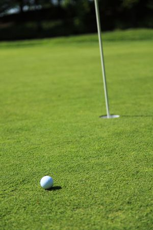 golf ball next to a flag on a green of a beautiful golf course with dramatic summer sky Stock Photo