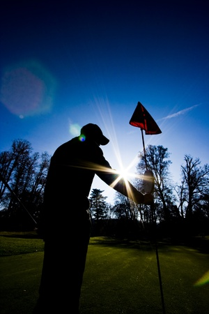 silhouette of a golf player pulling out the flag