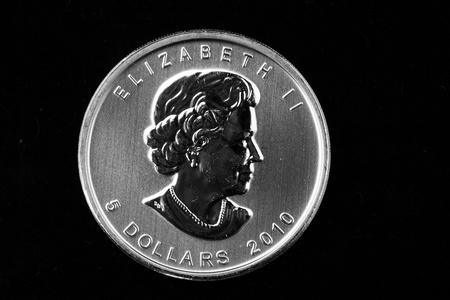 dolar: Hoja de arce canadiense de moneda de plata aislado en un fondo negro