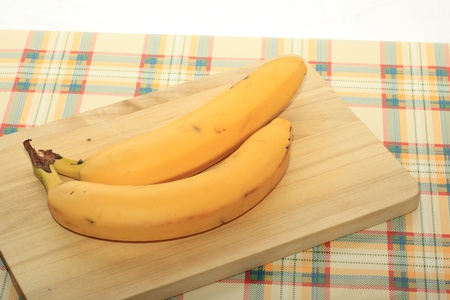 two bananas on a wooden plank on a table photo