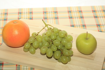 Fresh green grapes, apple and grapefruit on a table photo