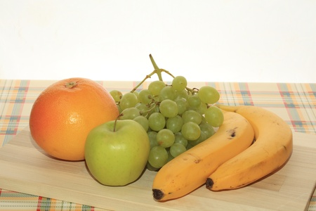 Fresh green grapes, apple, banana and grapefruit on a table Stock Photo - 12206086