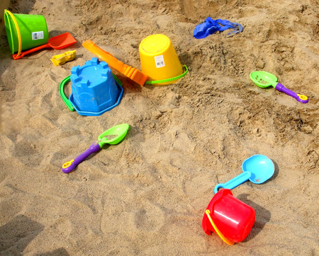 sifter: Colorful shovels and pails on the sandy beach.