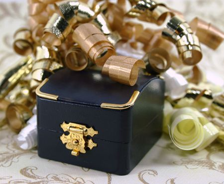 closed ribbon: A small closed navy blue jewelry box surrounded by curly gold, white and yellow ribbon.