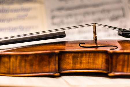 romp: The part of very rare and old violin on blurry background with musical notes with some ancient song.