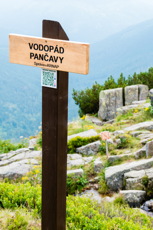 The wooden sign informs of Pancava Waterfall. On background, which is smooth blurry, there are, huge rocks, valley and faraway mountains. The sign is located in Giant Mountains in Czech Republic. Stock Photo