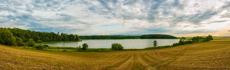 Beautiful place with beautiful lake, forest and field. Sunset on summer, panoramatic view.