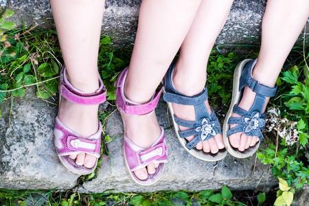 De benen van het jonge meisje met sandals. Voet in rode sandaal op stenen trappen. Groen gras.