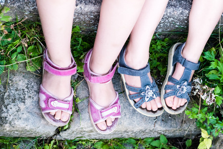 Young girls legs with sandals. Foot in red sandal on stone stairways. Green grass.